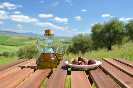 aceite de oliva: El aceite de oliva y pan en la mesa contra el paisaje de la Toscana. Italia