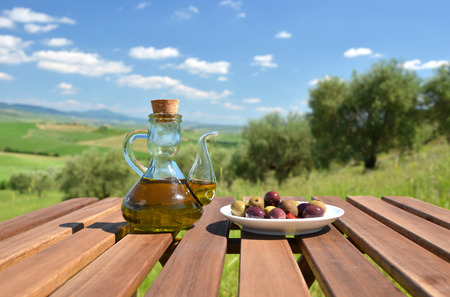 olive green: Olive oil and bread on the table against Tuscan landscape. Italy
