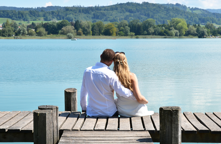 inlove: A couple on the wooden jetty at the lake. Switzerland Stock Photo