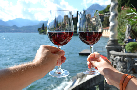 wine glass: Two wineglasses in the hands. Varenna town at the lake Como, Italy