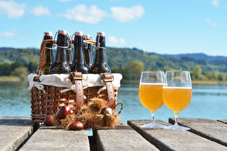 6 pack beer: Beer on the wooden jetty against a lake