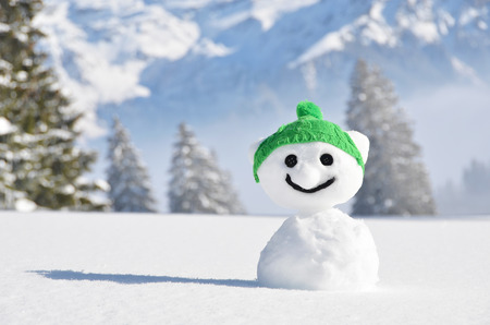 season greetings: Funny snowman against Swiss Alps