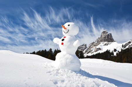 Funny snowman against Swiss Alps