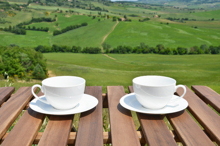 cups of coffee: Two coffee cups on the wooden table against Tuscan landscape, Italy