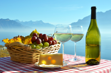 Wine, cheese and grapes against Geneva lake, Switzerland
