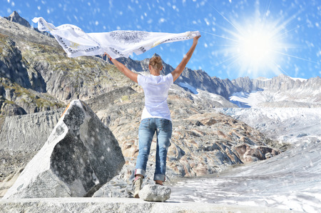flapping: Girl holding a flapping shawl against Rhone glacier. Switzerland
