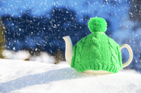 tea cosy: Tea pot in the knitted cap on the snow