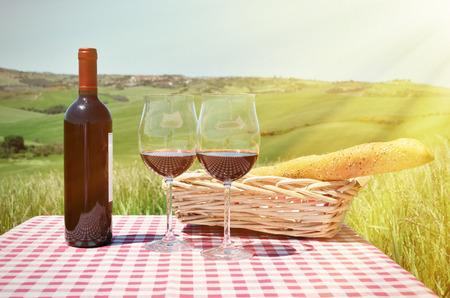 pan y vino: El vino tinto y pan en la tela a cuadros contra el paisaje de la Toscana. Italia Foto de archivo