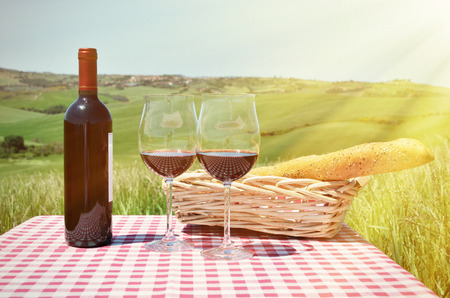 wine glass: Red wine and bread on the chequered cloth against Tuscan landscape. Italy