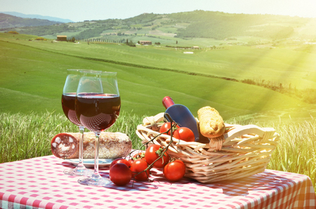 the tuscany: Red wine and bread on the chequered cloth against Tuscan landscape. Italy