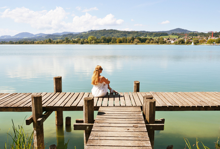 jetty: Girl on the wooden jetty at the lake. Switzerland