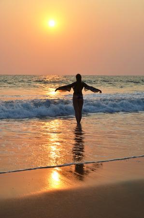 downshifting: Young woman meditating on Agonda beach. South Goa, India