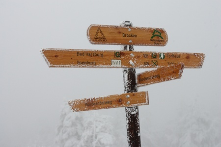 signpost with many directions and snow