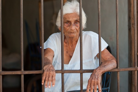 Elderly woman looking out of here house in Trinidad, Varadero, Aug 2009. Stock Photo - 8790797