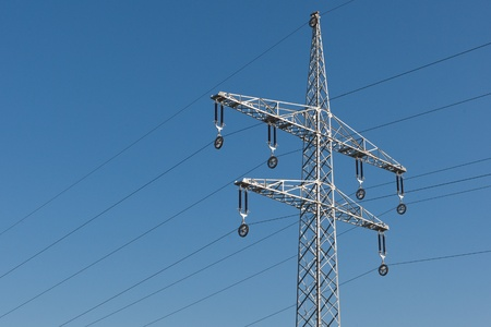 Electric power line tower in front  of blue sky