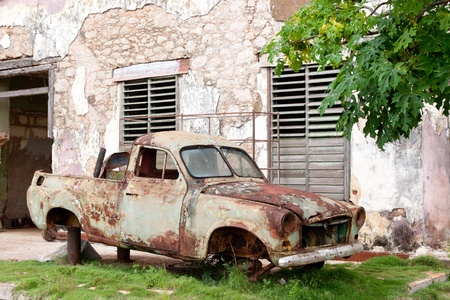 Very old car wreck, rusty and scrapped in front of old house Stock Photo
