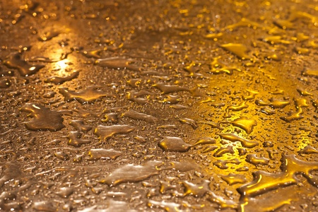 Metallic surface, shining in yellow evening light with raindrops on it Stock Photo