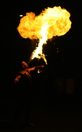Fire breathing street performance artist at night.
