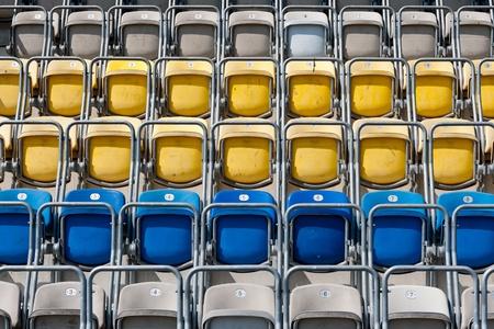 Colored stadium chairs. A field of empty stadium seats.