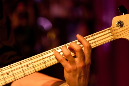 hand of a bass player while playing the bass, colorful background Stock Photo
