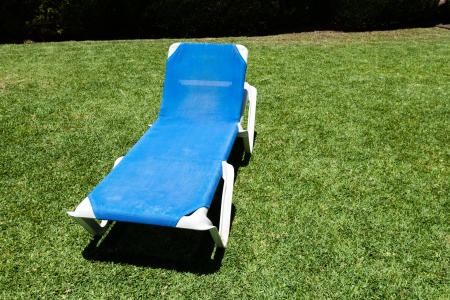 Blue lounger on a manicured green lawn to relax and enjoy the summer vacation reclining in the sunshine