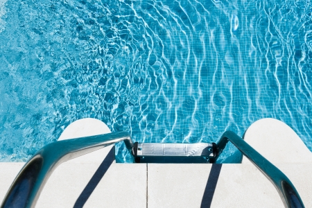 Overhead view of metal steps leading down into an inviting blue swimming pool with a mosaic bottom shimmering in the sunlight photo