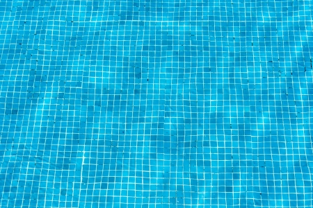 Turquoise blue swimming pool mosaic pattern on the floor of a pool shimmering in the reflections from the summer sun