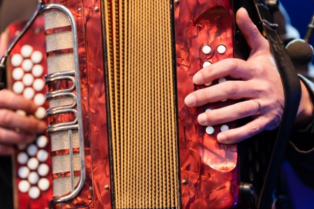 Closeup cropped image of the hands of a man playing a colourful red accordion musical instrument