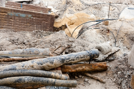 Image of some old and rusty pipes being taken out of the surface  Stock Photo