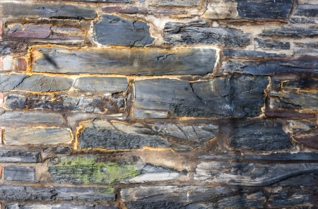 Wall made of natural stone fashioned into rectangular bricks with rough texture