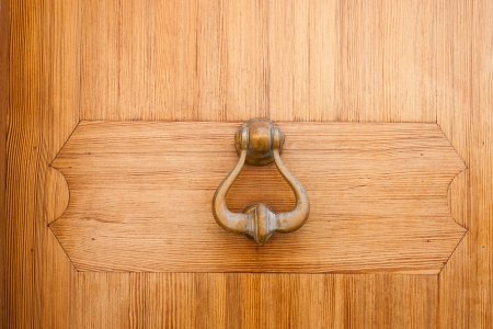 Brass door knocker hanging on a wooden door for gaining access or entry by creating a noise