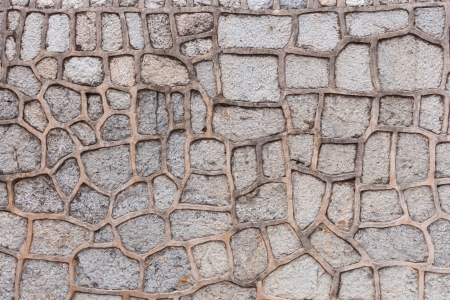 Background pattern of a stone wall with each rough natural stone surrounded by mortar to form a crazy paving pattern
