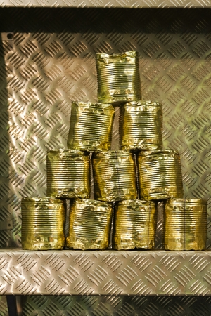 Old battered tin cans stacked in a pyramid on a metal shelf as a decoration or target