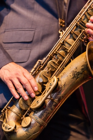 Man playing a brass tenor saxophone or sax during a live performance in an orchestra, a popular reed instrument in jazz, blues and country music