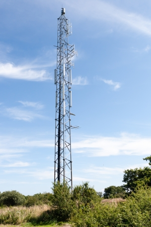 Tall lattice steel communications tower in the countryside with transmitters and receivers for relaying broadcasts and telecommunication