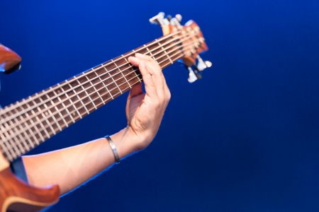 Woman playing an electric guitar with a view of her hand holding the strings on the neck of the instrument over the fingerboard on a blue background with copyspace
