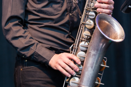 woodwind instrument: Close up view of the hands of a male saxophonist playing a tenor saxophone in an orchestra, a reed woodwind instrument popular in jazz, classical and blues music