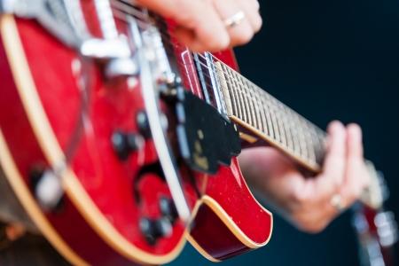 Close up view of a male guitarist playing an electric guitar with focus to the pickup of the guitar and the strings Stock Photo
