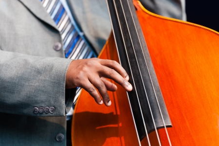 Close up of the hand of a man sitting playing a double bass in an orchestra, a large wooden stringed instrument played with a very low pitch popular in classical, jazz and blues genres of music Stock Photo