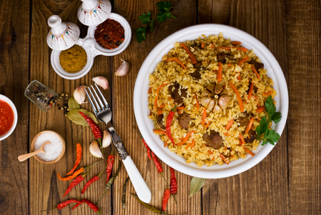 pilaf in a plate on wooden background, top view Stock Photo
