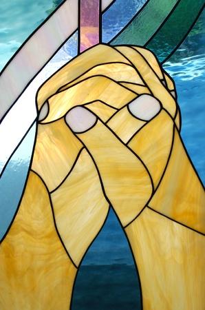 prayer hands: mani sul vetro colorato in chiesa a pregare Editoriali