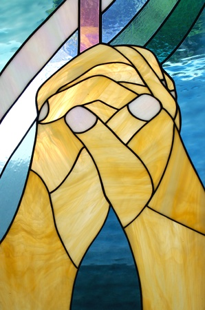 worship white: praying hands on stained glass in the church