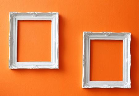 grunge photo frame: Two white vintage frames on orange wall  Stock Photo