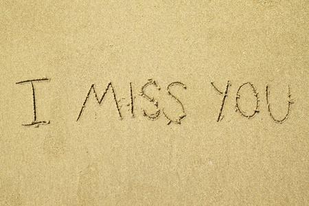 handwritten miss you in sand  photo