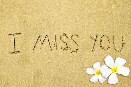 te extra�o: manuscrita te extra�o con flor de frangipani sobre arena  Foto de archivo