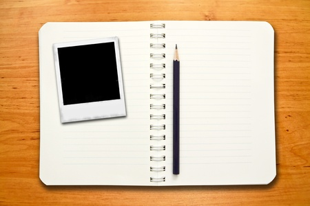 Classic instant photo frames on blank notebook with pencil photo
