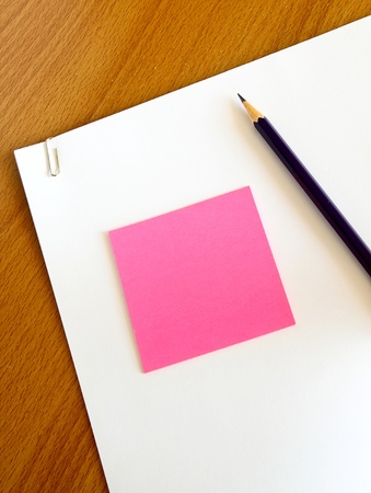 white paper with pencil and pink memo on wood table photo