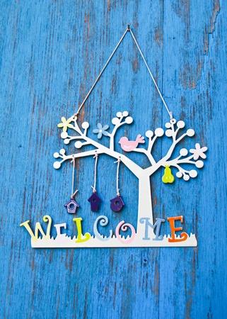 bienvenida: Palabra bienvenida en madera puerta azul