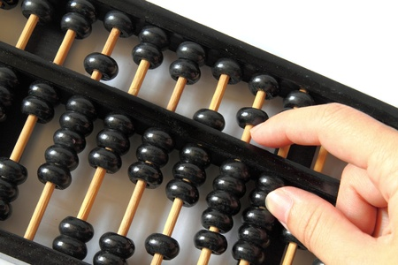 accountancy: hand and a wooden abacus with copy space
