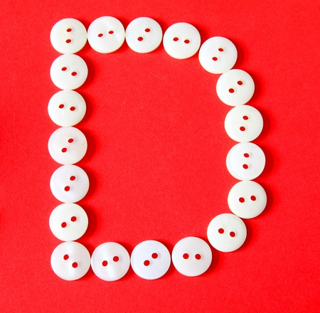 Letter D from buttons on a red background photo